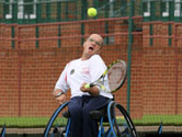 image of man in a wheelchair playing tennis