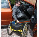 image of man getting out of a car into wheelchair